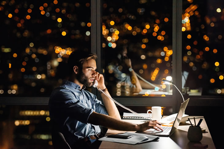 Man on phone in office with evening city view