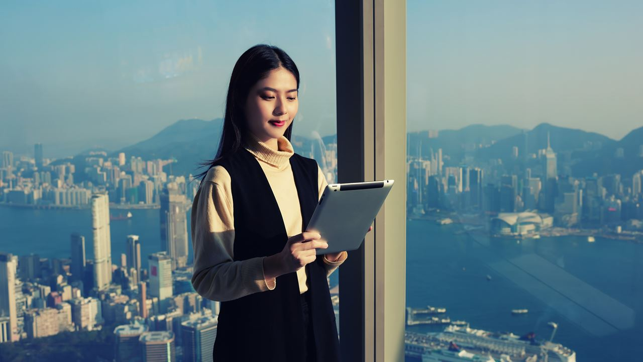Business lady looking at device with city backdrop