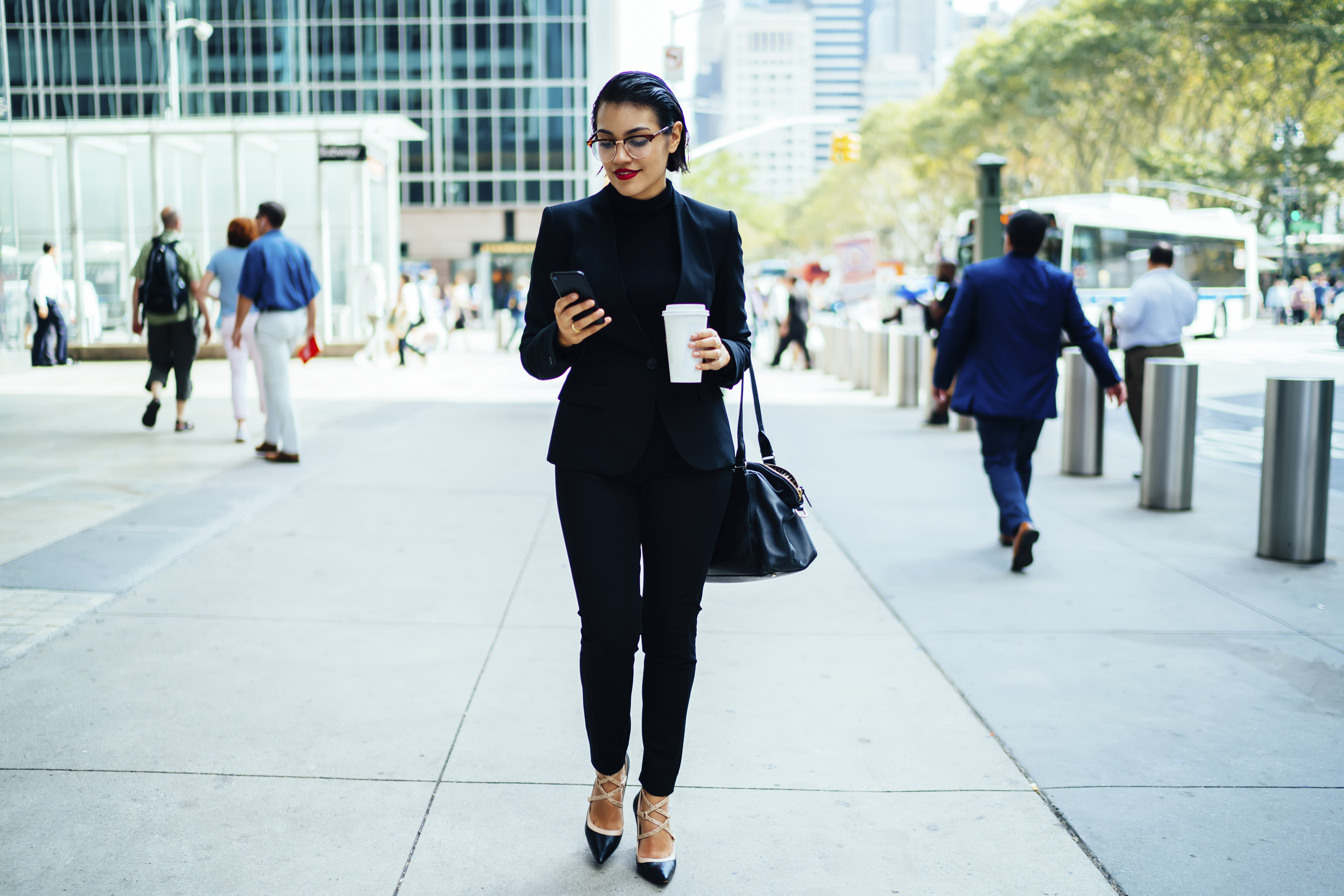 Woman looks at phone whilst walking