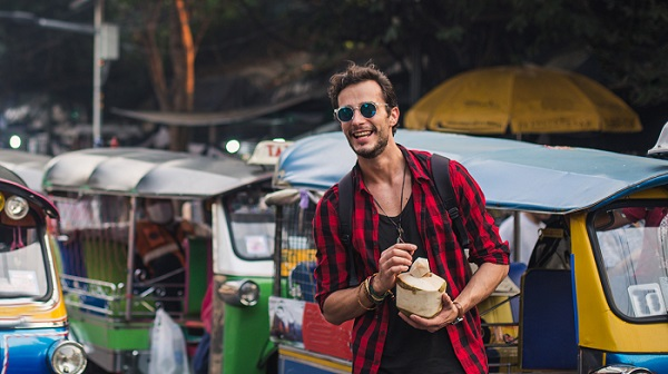 Backpacker with coconut in Thailand